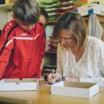 Lehrerin kontrolliert vor einem Schüler seine Arbeit und sie gehen gemeinsam Fehler durch.