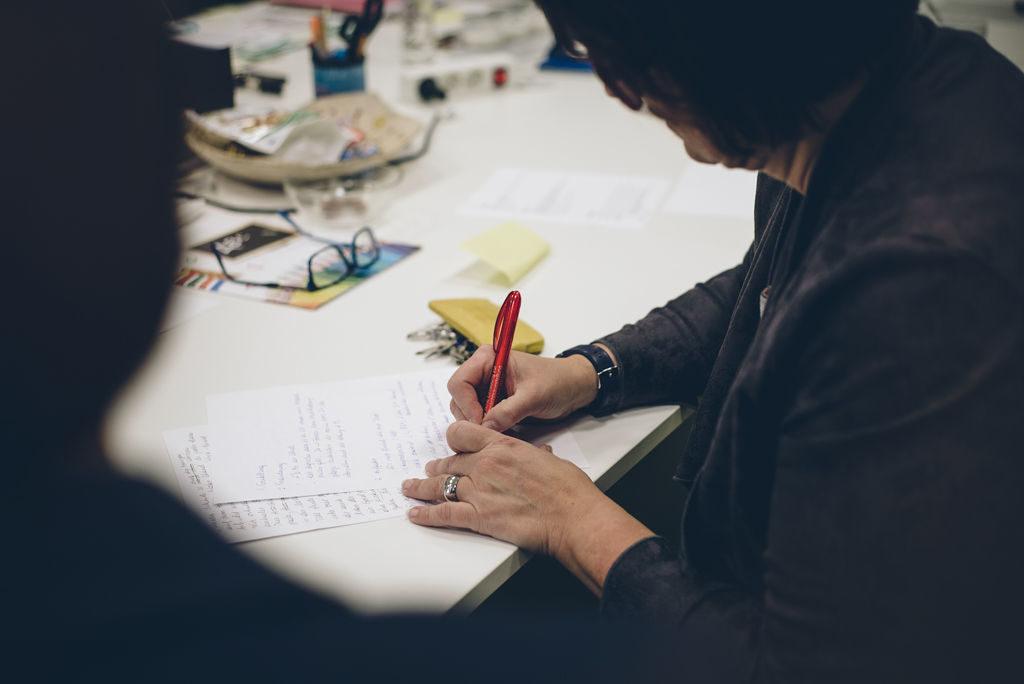 Eine Frau, fotografiert von schräg hinten, so dass man ihr Gesicht nicht sieht, sitzt an einem Tisch und macht Notizen.