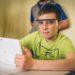 Schüler sitzt mit Schutzbrille und Tablet am Tisch und grinst in die Kamera.