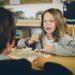 Mädchen hat eine Landkarte mit Fähnchen vor sich und spricht zur Lehrerin