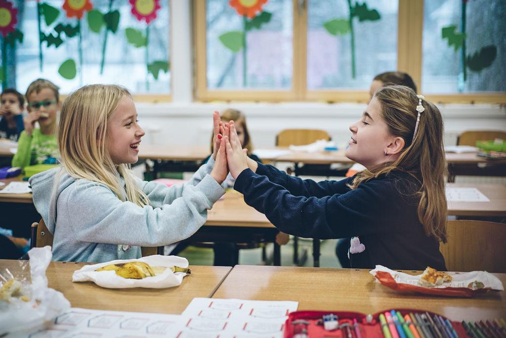 Zwei Schülerinnen klatschen im Klassenzimmer gegenseitig in die Hände.
