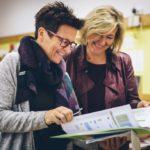 Zwei Lehrerinnen besprechen sich mit Unterlagen in der Hand