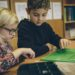 Eine Schülerin und ein Schüler sitzen gemeinsam an einem Tisch im Klassenzimmer und lernen.