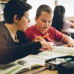 Zwei Schüler sitzen mit einem Lehrbuch am Tisch in einer KLasse und lernen gemeinsam.