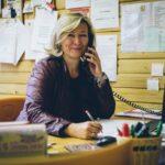 Rektorin telefoniert am Schreibtisch