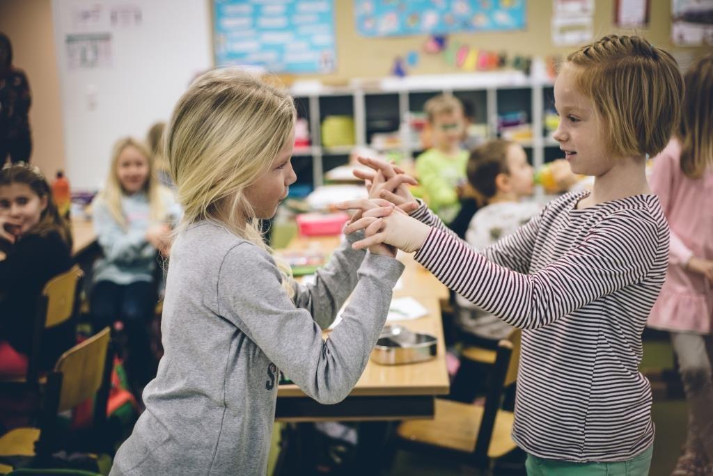Zwei Volksschülerinnen stehen sich gegenüber und verschränken in der Luft miteinander die Hände