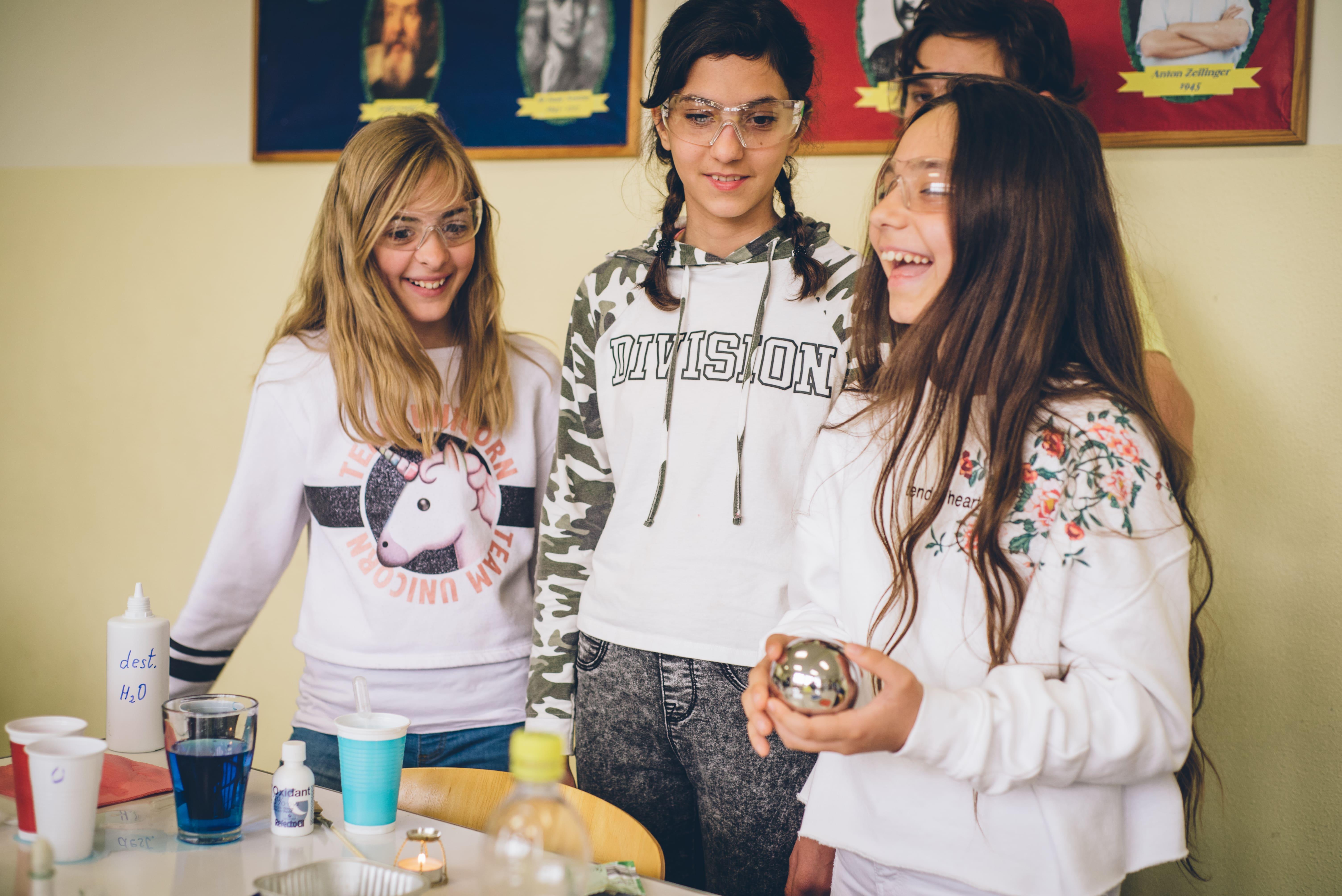 Drei Mädchen mit Schutzbrille beim Experiment
