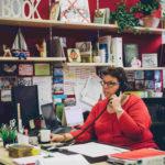 Eine Schulleiterin hinter ihrem Schreibtisch beim telefonieren