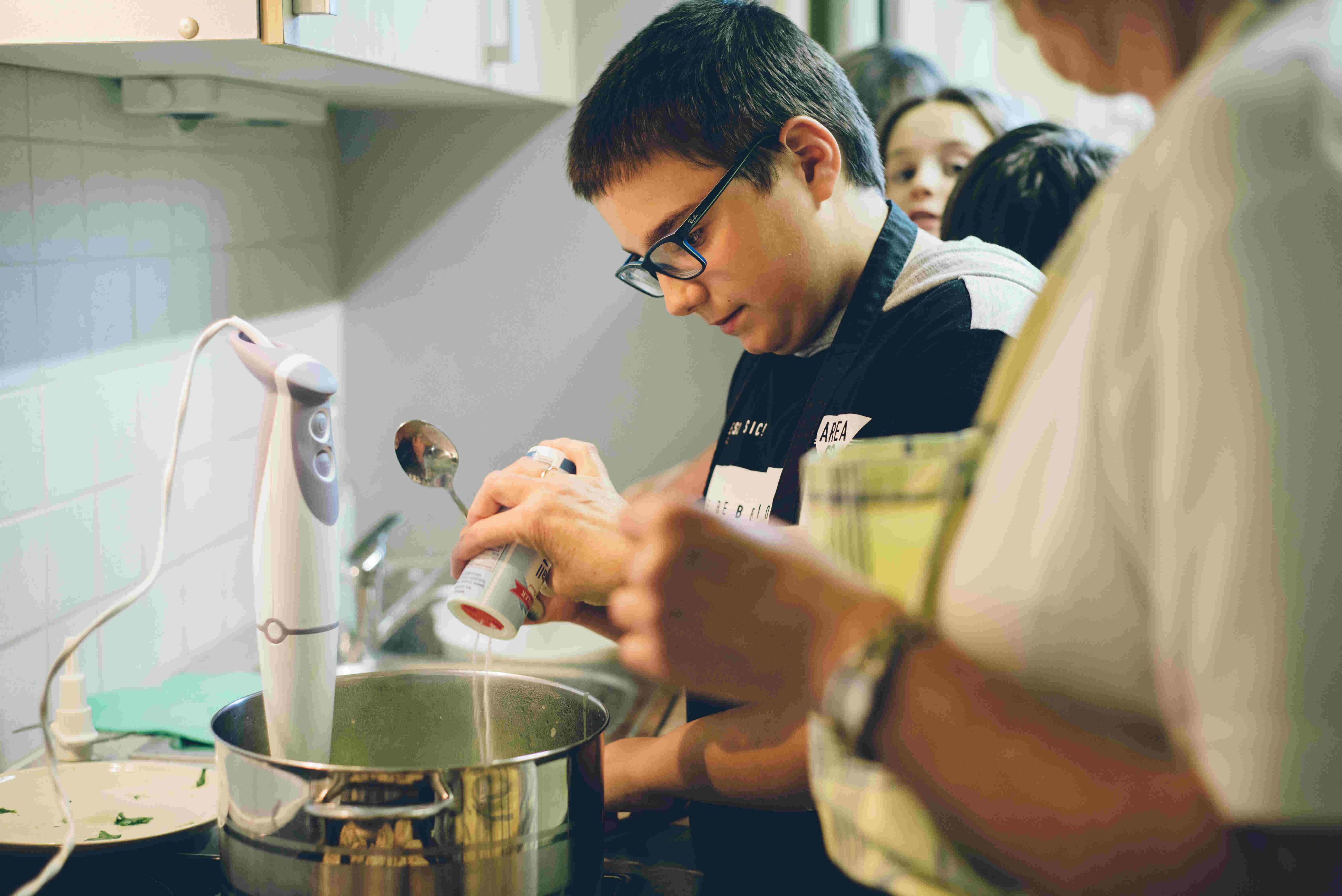 Lehrerin und ein Schüler beim kochen