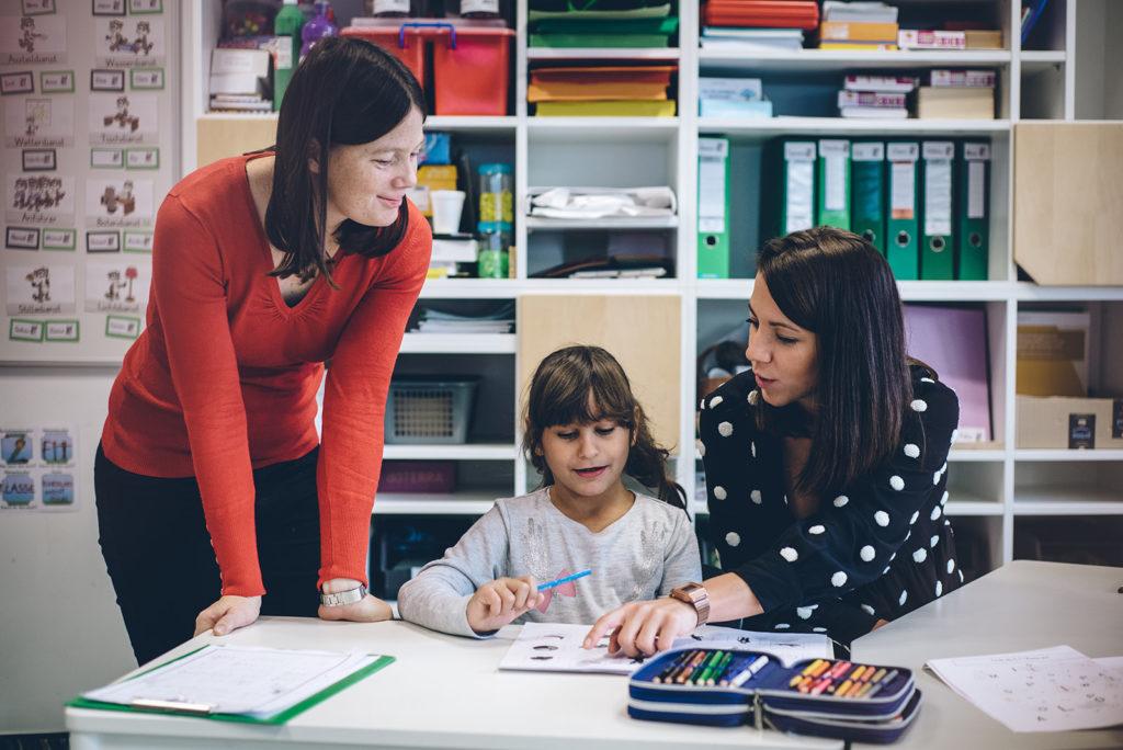 Zwei Lehrerinnen unterstützen eine Volksschülerin bei ihrer Aufgabe.