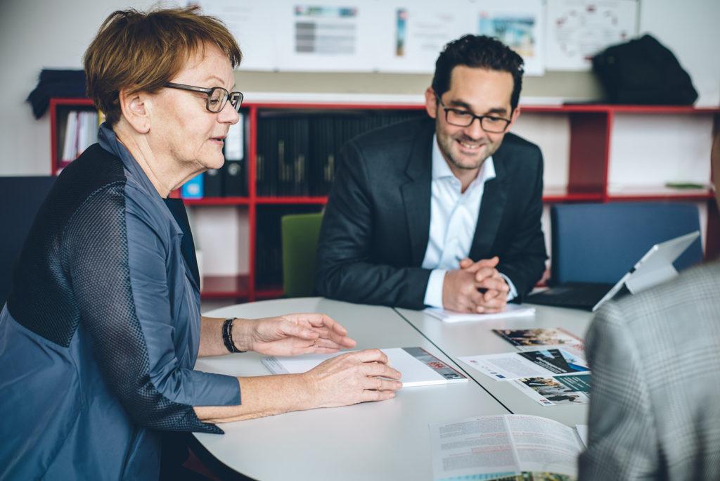 Die Direktorin sitzt gemeinsam mit einem Lehrer bei einer Besprechung.