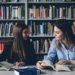 Zwei Schülerinnen sitzen vor einem Bücherregal und lesen in ihren Büchern.
