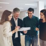 Direktor bei einer Besprechung mit einem Lehrer und zwei Lehrerinnen im Konferenzzimmer.