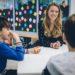 Eine Lehrerin sitzt mit Kindern am Tisch und unterhält sich.
