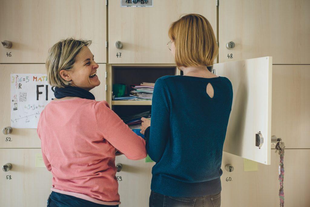Zwei Lehrerinnen stehen zusammen und räumen ihren Schrank ein und lachen dabei.