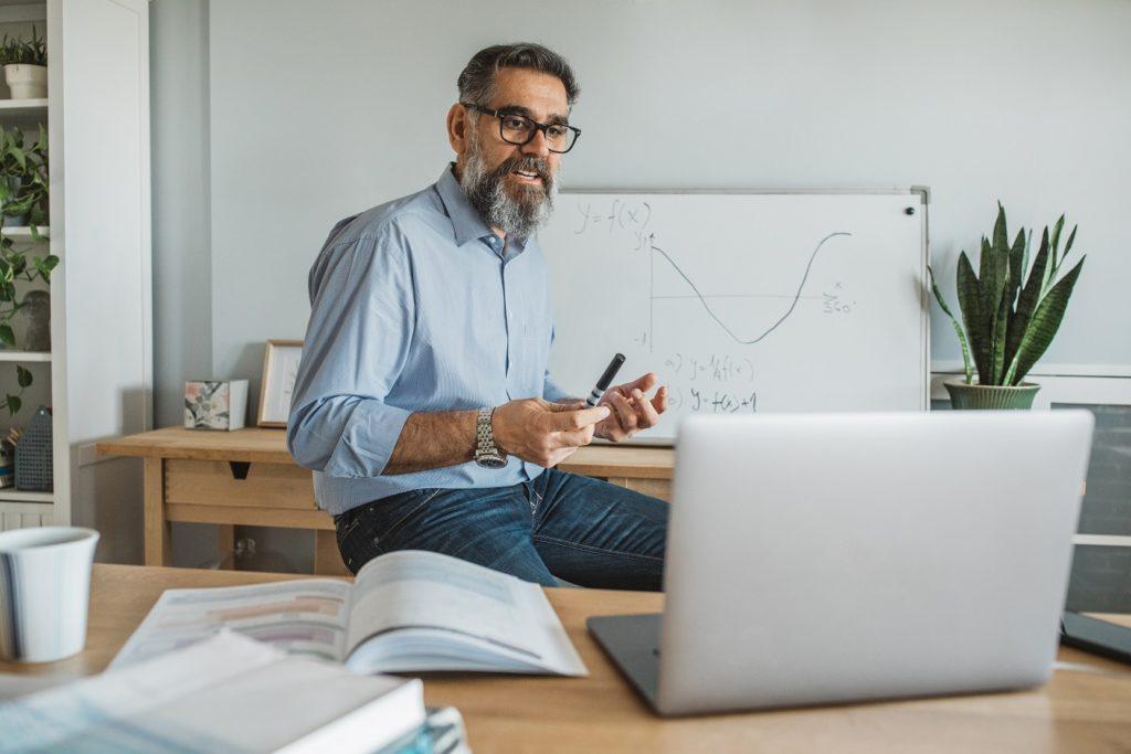 Lehrer unterrichtet zuhause über Laptop eine Mathematikklasse. Im Hintergrund steht ein weißes Board, auf dem eine Funktion aufgezeichnet ist.