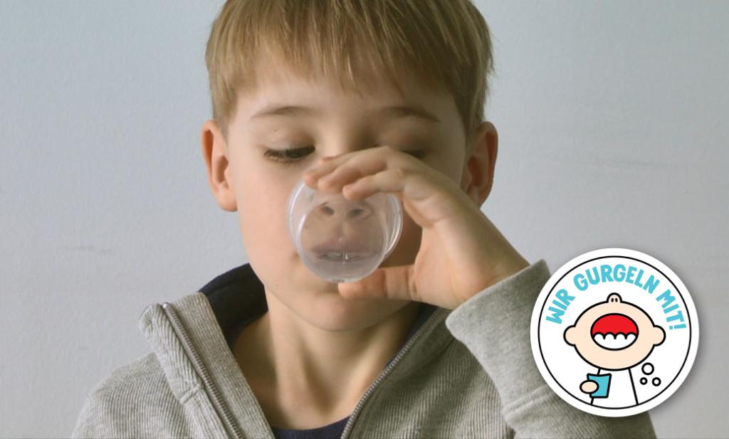 Ein Kind, dass eine Flüssigkeit über einen Becher aufnimmt