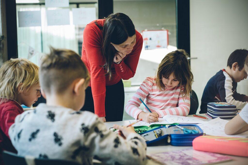 Eine Lehrerin schaut gemeinsam mit einem Kind in ein Heft