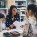 Eine Lehrerin sitzt mit zwei Kindern beisammen